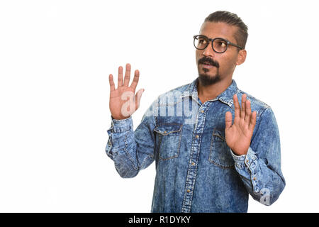 Young Indian man looking shocked studio portrait against white background