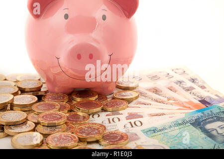 Pink Piggy bank on lots of pound notes and pound coins - Stock Photo