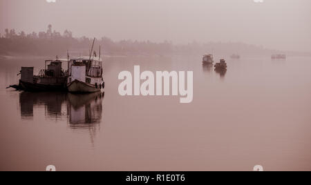 Anchored fishing boats on a foggy morning in the Subarbans, West Bengal, India - Stock Photo