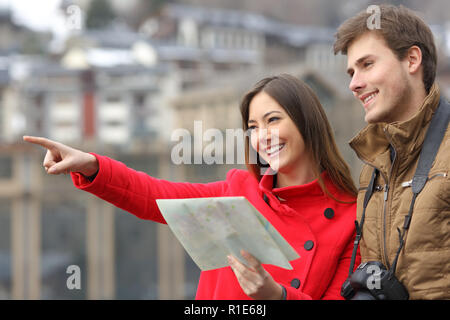 Happy couple of tourists holding a paper map and pointing away in the street of a town - Stock Photo
