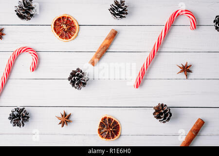 pattern of christmas candies, pine cones and dried oranges on white wooden background. Christmas decorations - Stock Photo
