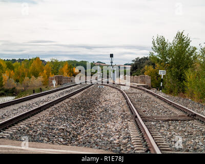 Crossroads on train tracks that go through a landscape in autumn with clouds in the sky - Stock Photo