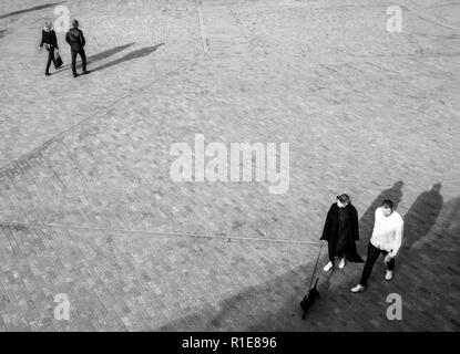 Blurred unrecognizable people from above walking on an open space square with shadows projecting on the floor - Stock Photo