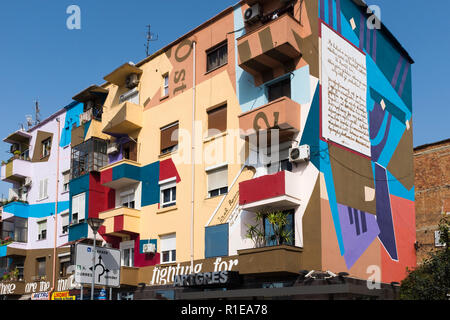 Brightly painted and colored buildings brighten old buildings in Tirana, the capital city of Albania. - Stock Photo