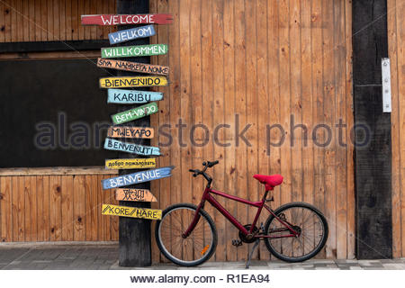 Red Bike Next to a Post with Welcome Signs in Several Different Languages.  English, Afrikaans, German, Xhosa, Spanish, Swahili, Portuguese, Oshiwambo - Stock Photo