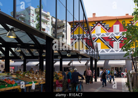Brightly painted and colored buildings brighten old buildings by the city market in Tirana, the capital city of Albania. - Stock Photo