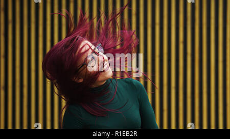 Cute young girl dancing on background of simple geometric pattern. Girl has eggplant hair flying in motion. She is in dark green dress. Free lifestyle - Stock Photo