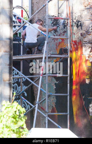 To promote their '21st Century Breakdown' album and world tour, the band Green Day organized for several large wall murals to be painted in various spots across the city of Sydney, Australia. Due to the fact that the installation of the murals was not approved by Sydney Council, the wall paintings were soon removed. Pictured: a worker removes a Green Day mural from a wall in Liverpool Lane at the corner of Riley Street in Darlinghurst. - Stock Photo