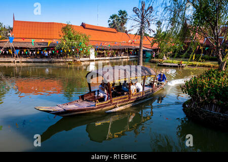 Floating market with a boat full of tourists. - Stock Photo