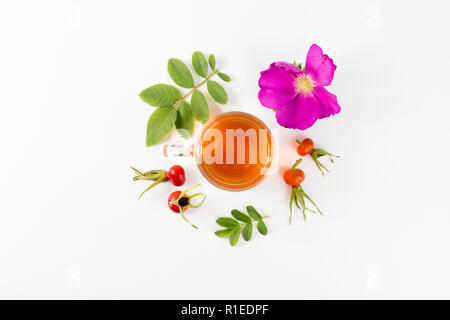 Flat lay view of the rose hip or rosehip, also called rose haw and rose hep tea in clear glass cup, raw berries, blossom and leaves for decoration on - Stock Photo