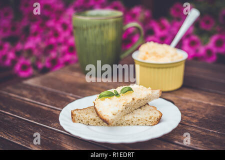 Yellow delicious egg and mayonnaise paste on whole wheat bread, breakfast snack recipe, pink flowers on the background, wooden base. - Stock Photo