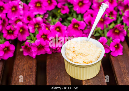 Yellow delicious egg and mayonnaise paste in yellow cup, spoon sticking out, breakfast snack recipe, pink flowers on the background, wooden base. - Stock Photo