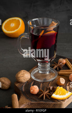 Winter composition. Mulled wine in glasses at black background. Fir wreath, tray with orange, cinnamon, nuts, cone and spices near. - Stock Photo