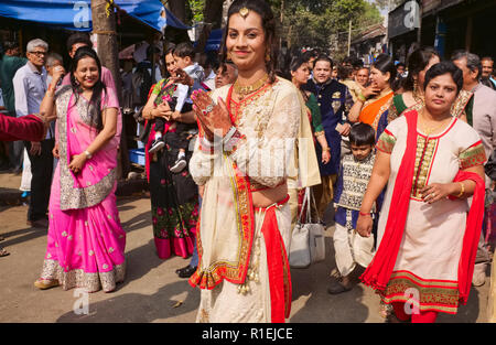 A Gujarati wedding party in Matunga, a suburb of Mumbai, India, spills out into the street, the bride up front with traditionally henna-painted hands - Stock Photo