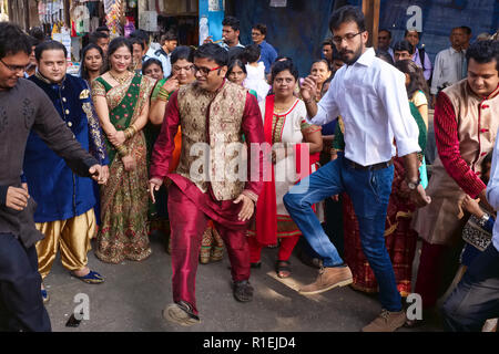 A Gujarati wedding party in Matunga, a suburb of Mumbai, India, spills out into the street, the participants dancing in the street and cheering - Stock Photo