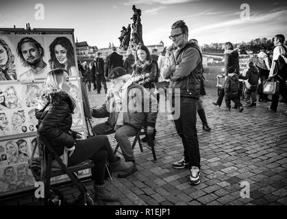 Tourists on Charles Bridge Prague, Czech Republic, with street artist getting painted in black and white - Stock Photo