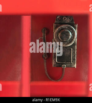 traditional classic red phone box, in which conventional wall dial rotary phone is attached, ready to dial call. Retro furniture, Interior vintage des - Stock Photo