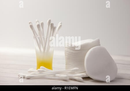 Clean cotton pads and sticks in a glass for the body on a light background, the concept of body care - Stock Photo
