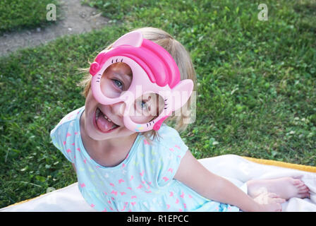 Happy adorable little girl making funny face with mask on it and looking into the camera - Stock Photo