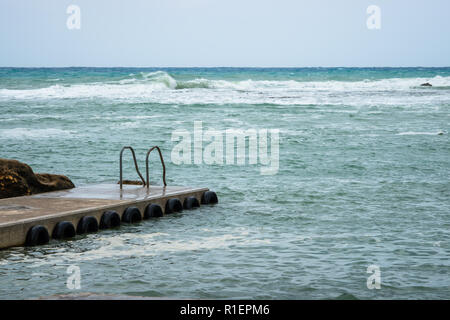 Quiet boat pier in Marsalforn Xwejni Bay Gozo.Tyre as a fender. Calm sea bay. While the sea is rough. Leader for people to swim. - Stock Photo