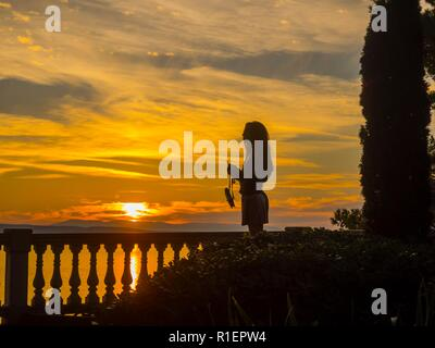 Teen girl in park silhouette side-view body against sunset sky waiting holding purse - Stock Photo