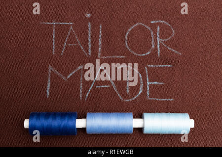Tailor made written on brown fabric as background underlined with blue thread spools - Stock Photo