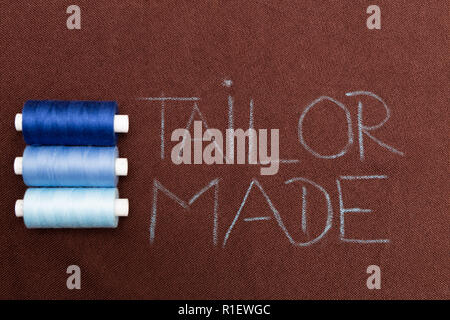 Blue thread bobbins near tailor made text written with chalk on brown material - Stock Photo