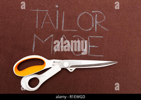 Scissors underlining tailor made text on brown fabric as background - Stock Photo