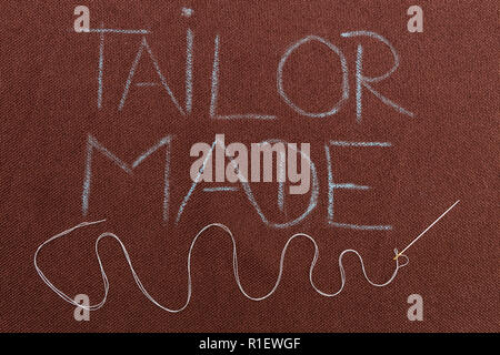 Tailor made blue text on brown fabric background underlined with winding thread in needle - Stock Photo