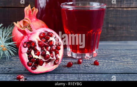A glass of fresh pomegranate juice with ripe pomegranate fruits on wooden table. Vitamins and minerals. Healthy drink concept. Close up - Stock Photo