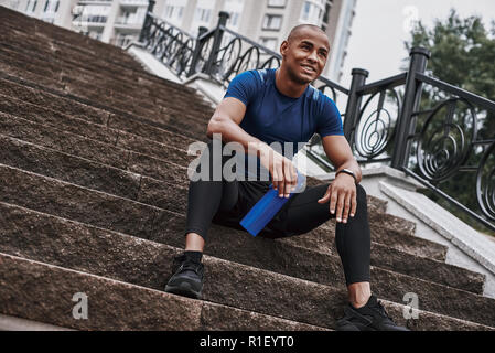 Smiling sportsman is holding water bottle while sitting on steps with outdoors - Stock Photo