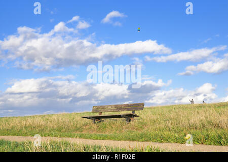 An empty wooden bench on Hampstead Heath with a colourful kite flying in the background - Stock Photo