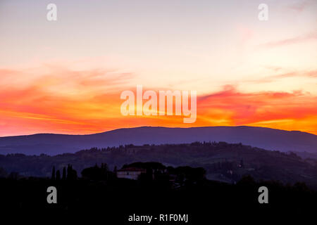 Amazing coloured sunset in Tuscany Italy with red clouds and blue ground during the blue hours. Beautiful landscape with colors and feeling - Stock Photo