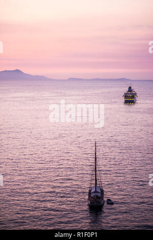 Touristic cruise boat in the middle of a quiet sea after the sunset with a pink coloured nice sky for all the people wander to travel and enjoy the va - Stock Photo
