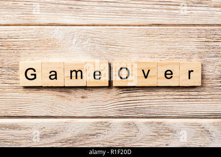 game over word written on wood block. game over text on table, concept. - Stock Photo