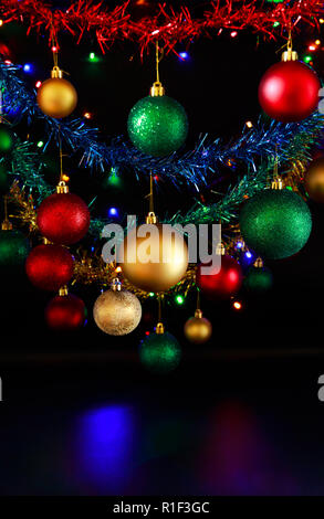 Close up of hanging Christmas decorations and Christmas/fairy lights against a black background. - Stock Photo