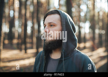 a young man with a beard walks in a pine forest. Portrait of a brutal bearded man in a hood Homeless - Stock Photo