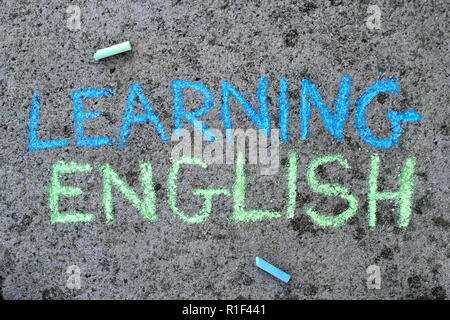 Colorful chalk drawing on asphalt: text LEARNING ENGLISH - Stock Photo