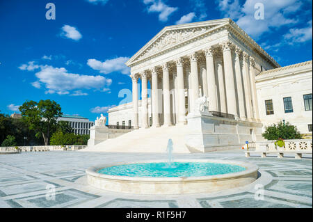 Bright scenic view of the neo-classical facade of the United States Supreme Court building from the plaza fountain under blue sky - Stock Photo