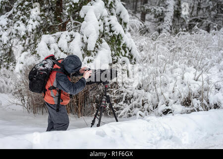 Behind the scene. Cameraman with video camera on tripod, shooting the film scene at outdoor location, on nature, forest, cold winter snowy day - Stock Photo
