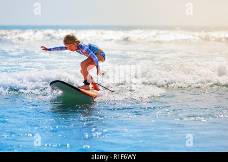 Happy baby girl - young surfer ride on surfboard with fun on sea waves. Active family lifestyle, kids outdoor water sport lessons, swimming activities