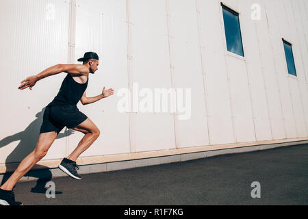 Sporty man runner running in city sreet. Sport, health, fitness, jogging - Stock Photo