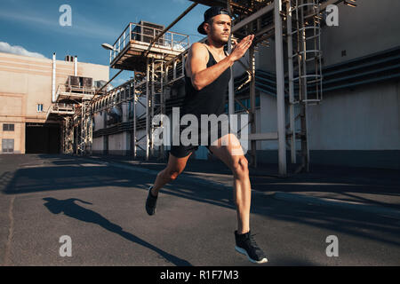 Sporty man running fast in industrial city background. Sport, athletics, fitness, jogging activity - Stock Photo