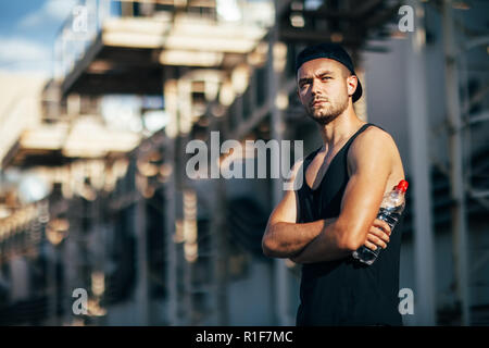 Serious handsome man posing on industrial background, hold bottle of water in hand - Stock Photo