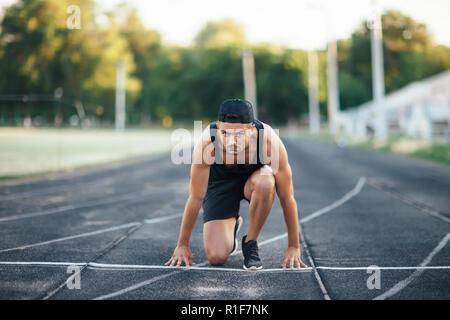 Runner on the start. Sprinter on the start line of the track in stadium - Stock Photo