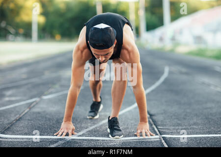 Runner man on the start. Sprinter on the start line of the track in stadium - Stock Photo
