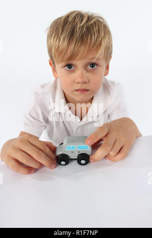 Adorable little boy playing with a small wooden car toy - Stock Photo