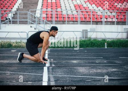Athlete man in running start pose on the running track in stadium - Stock Photo