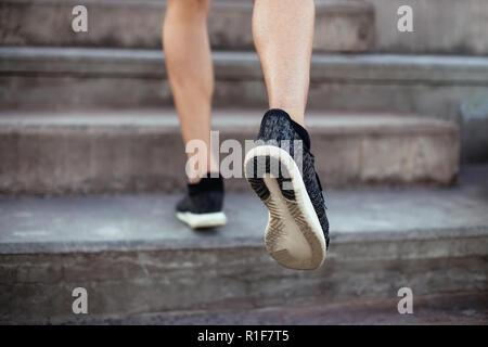 Close up of male feet in sneakers walking up the stairs. Athlete man legs running up - Stock Photo