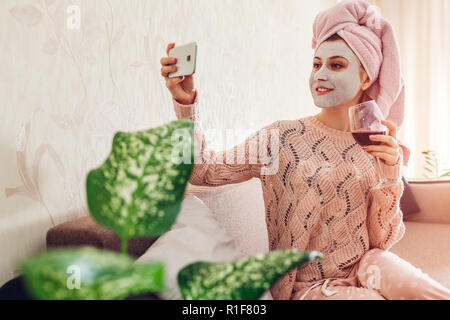 Young woman with facial mask applied drinking wine while taking selfie on couch. Relaxing at home. Girl having fun - Stock Photo